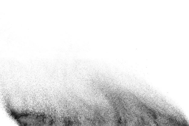 Explosão do pó preto de encontro ao fundo branco. partículas de poeira preta espirrando.