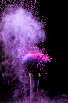 Explosão vibrante de maquiagem em pó com pincel em fundo escuro