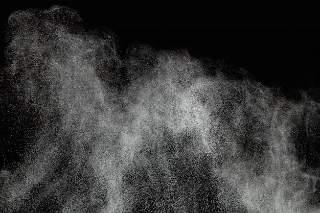 Explosões abstratas do pó isoladas no fundo preto.