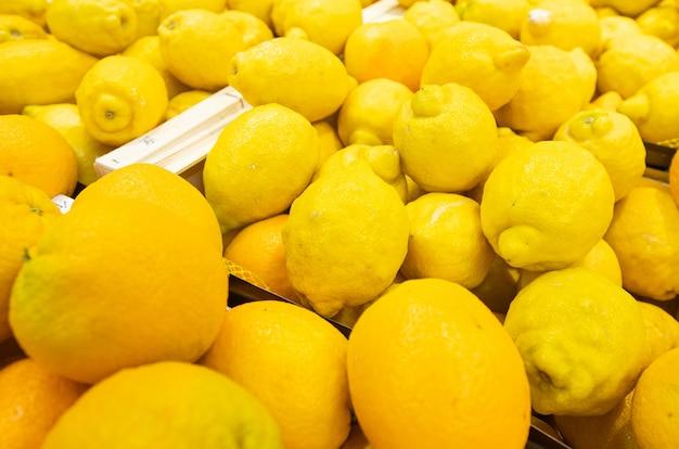 Exposição de frutas limão amarelo brilhante em caixas de madeira no mercado do fazendeiro ou mercearia. agricultura