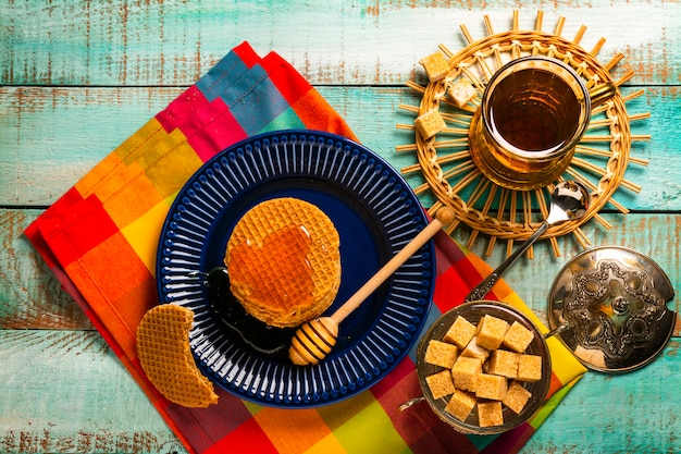 Exposição de waffles caseiros frescos com mel, caramelo, na mesa de madeira verde.