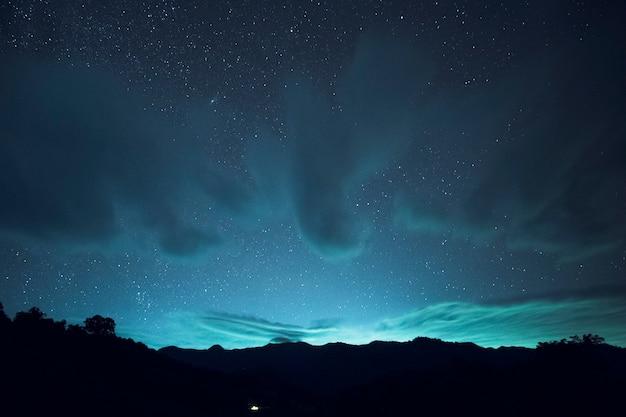 Exposição longa e iso alto tiro de estrela e nuvem sobre a montanha à noite. efeito de tom azul. eu