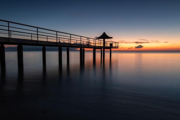 Exposição longa incrível do cais sobre o mar calmo no pôr do sol.