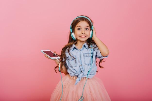 Expressando a positividade de criança feliz ouvindo música através de fones de ouvido azuis isolados no fundo rosa. menina bonita com longos cabelos castanhos sorrindo para a câmera com saia de tule