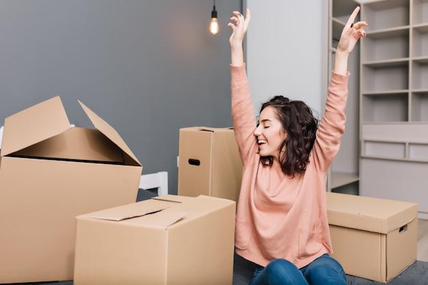 Expressando emoções verdadeiras brilhantes, positividade de uma jovem mulher bonita com cabelo curto morena encaracolado na cama cercam caixas de papelão no apartamento moderno. gostando de se mudar, felicidade na nova casa