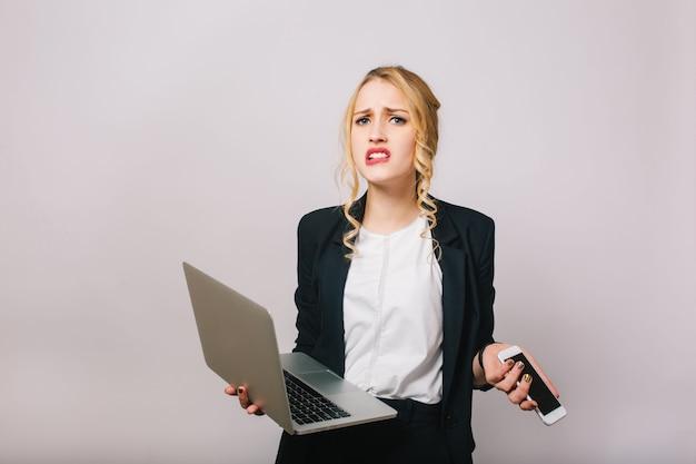 Expressando emoções verdadeiras chateadas de uma empresária loira. trabalhador de escritório moderno, laptop, telefone, secretária, tendo problemas, corporativo, isolado