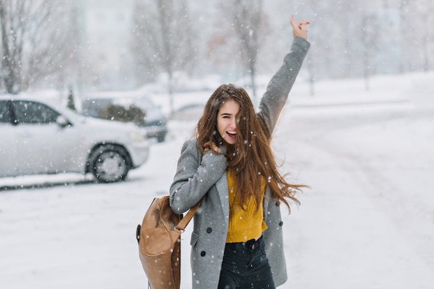 Expressando felizes emoções verdadeiras positivas de mulher andando em tempo nevando no inverno na rua. mulher incrível e animada com longos cabelos castanhos, desfrutando da queda de neve, se divertindo.