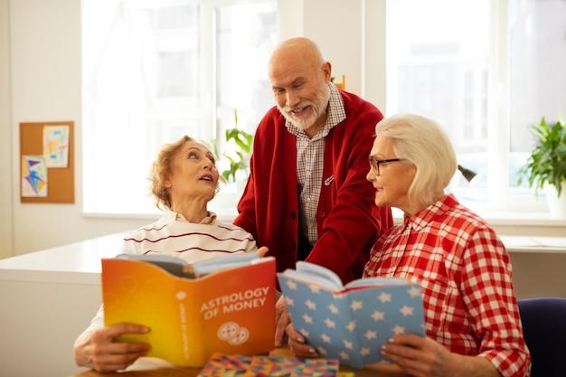 Expressando opiniões. um bom homem idoso sorrindo enquanto falava de livros com os amigos