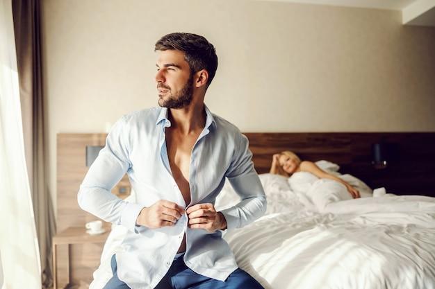 Expressando ternas emoções cheias de paixão em um quarto de hotel. a bela adormecida está deitada na cama e olhando para um homem bonito e bem vestido se preparando para ir a uma reunião de negócios. paixão de amor