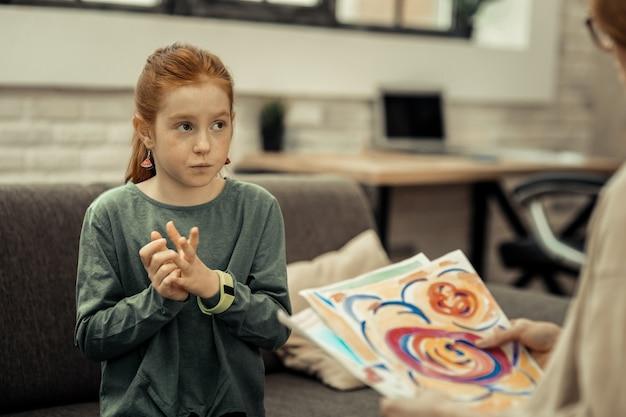 Expressão artística. menina simpática e atenciosa falando sobre sua pintura durante uma sessão com uma psicóloga profissional