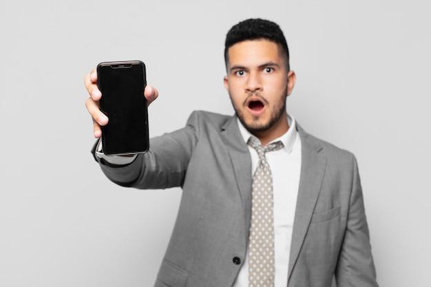 Expressão assustada do empresário hispânico e segurando um telefone