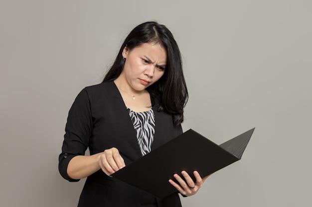 Expressão confusa de mulher de negócios enquanto olha para a pasta