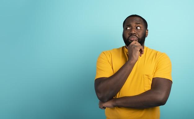 Expressão confusa e pensativa de um menino negro com muitas perguntas. parede de cor ciano