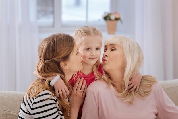 Expressão de amor. linda garota alegre e bonita abraçando a mãe e a avó e sorrindo enquanto é beijada