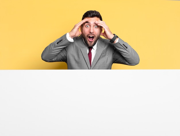Expressão de jovem empresário bonito espantado, surpreso ou chocado