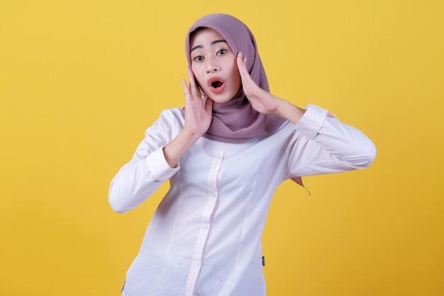Expressão de mulher asiática chocada, vestindo camisa casual e hijab