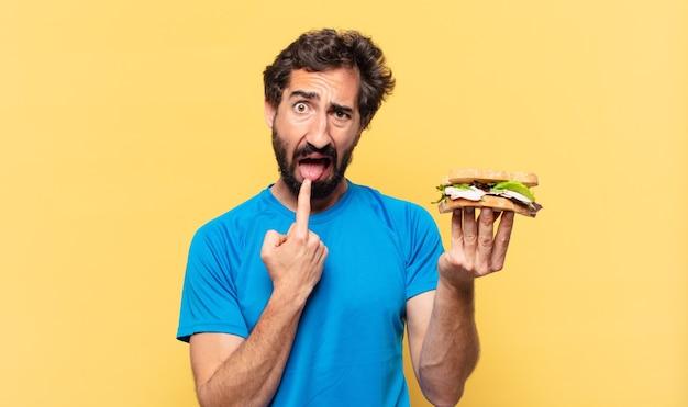 Expressão de raiva de jovem atleta barbudo maluco, segurando sanduíche