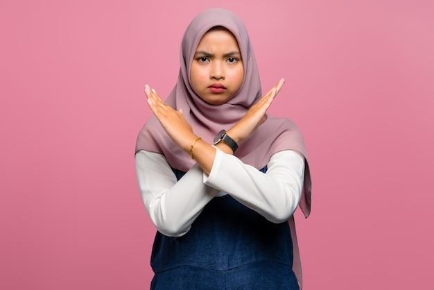 Expressão de rejeição de jovem asiática cruzando os braços e fazendo sinal negativo