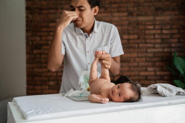 Expressão do pai ao trocar fraldas para o bebê