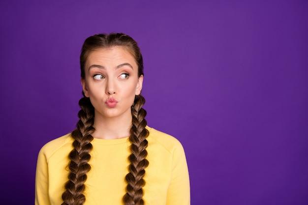 Expressão engraçada senhora com longas tranças penteado enviando beijos no ar, procurando astuto espaço vazio vestir pulôver amarelo casual isolado parede cor roxa