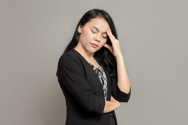 Expressão estressada de mulher de negócios enquanto segura sua cabeça e fecha os olhos