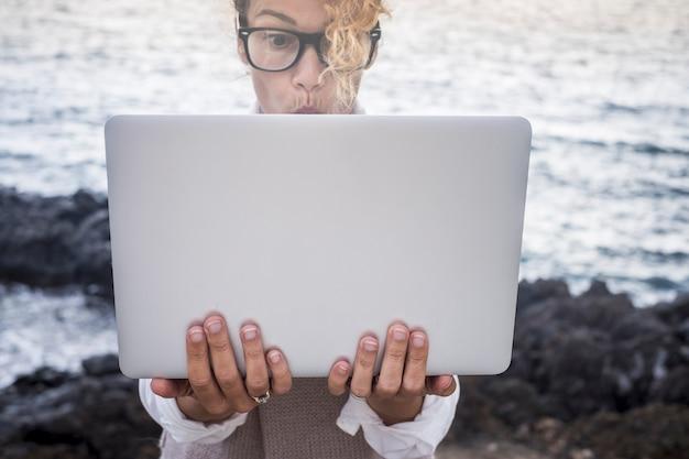 Expressão facial surpresa para uma bela jovem caucasiana trabalhando em um laptop em um escritório alternativo ao ar livre na costa perto das ondas do mar