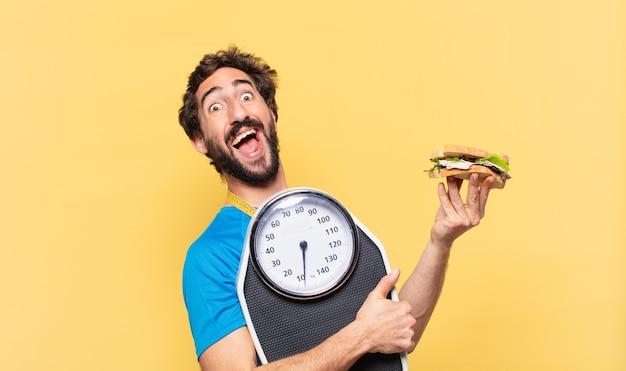 Expressão feliz de jovem atleta barbudo maluco, segurando sanduíche e balança