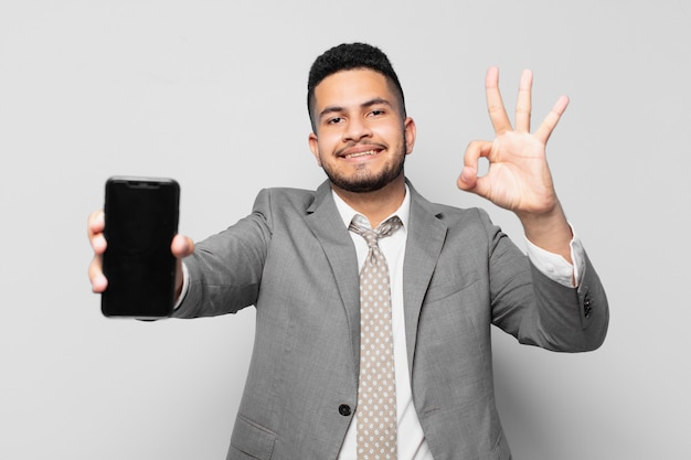 Expressão feliz do empresário hispânico e segurando um telefone