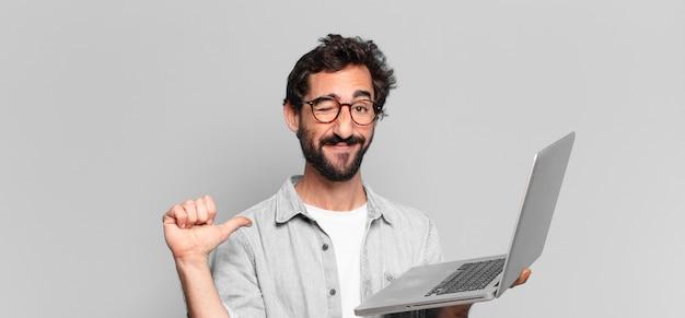 Expressão orgulhosa de jovem barbudo louco. conceito de laptop
