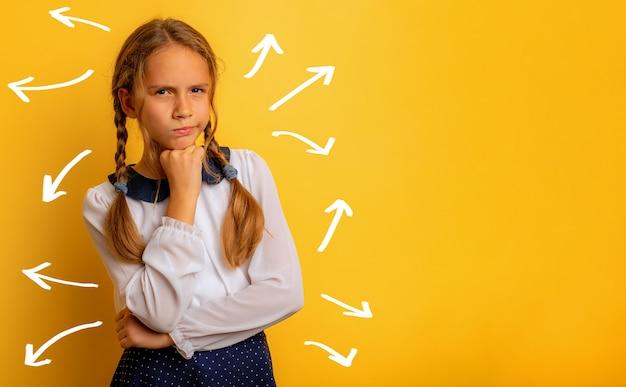 Expressão perplexa e pensativa de uma menina em um fundo amarelo