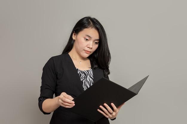 Expressão plana de mulher de negócios enquanto olha e segura uma pasta