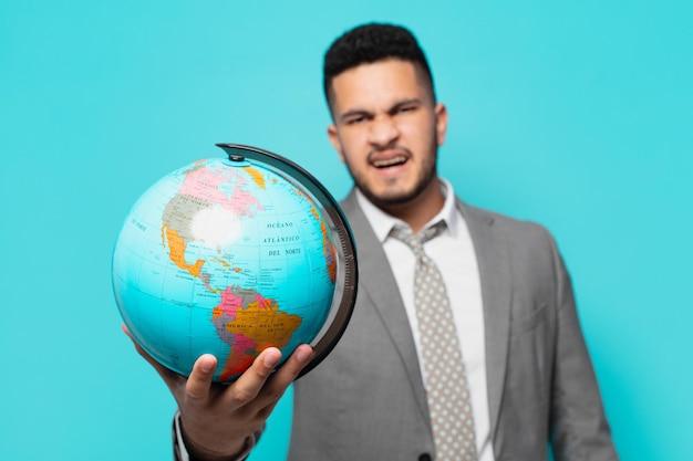 Expressão zangada do empresário hispânico e segurando um modelo de planeta mundial