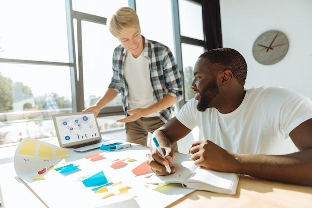 Expresse suas idéias. homem afro-americano profissional positivo fazendo anotações e sentado à mesa enquanto trabalhava com seu jovem colega