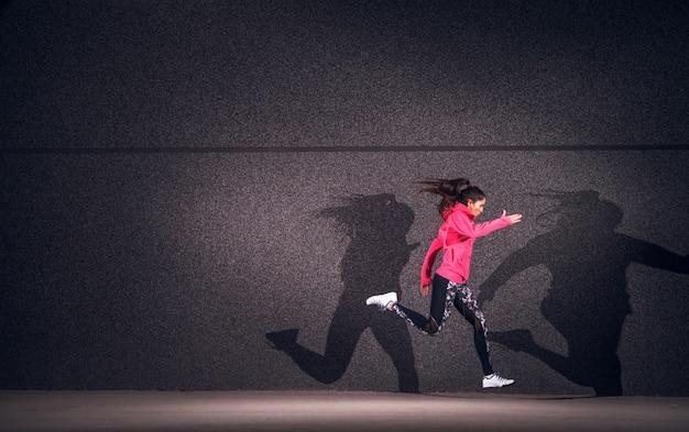 Expressionismo de ajuste linda mulher correndo com sombra dupla.
