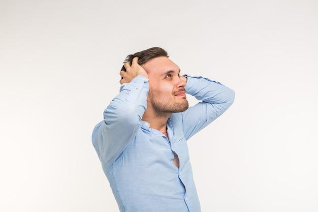 Expressions and people concept - retrato de um jovem barbudo de mãos dadas na cabeça dele, isolado sobre uma parede branca.