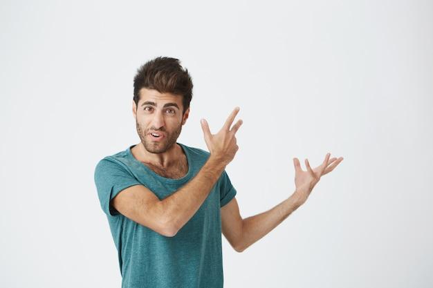 Expressivo cliente espanhol jovem e bonito, em roupas casuais, gesticulando e apontando no espaço livre para o seu anúncio. copie o espaço.