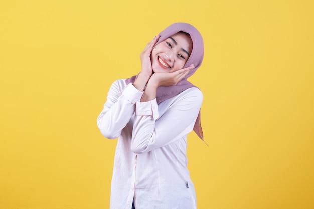 Expressivo e atraente mulher asiática exclama de felicidade, mantém as mãos nas bochechas, olha alegre
