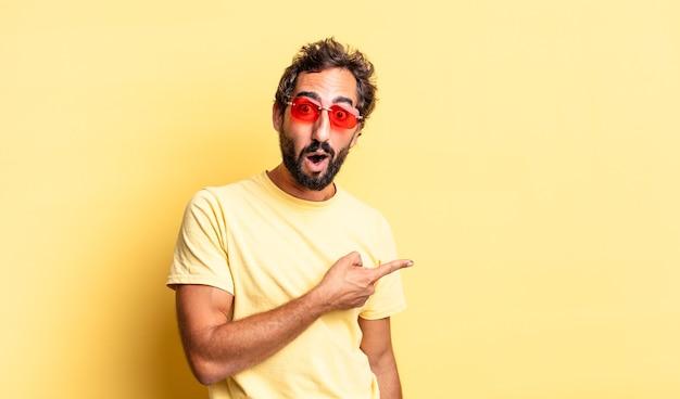 Expressivo homem barbudo louco usando óculos escuros e um espaço de cópia contra a parede amarela