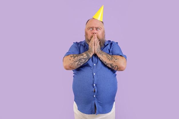 Expressivo homem barbudo surpreso com excesso de peso em uma camisa apertada segurando a boca em pé sobre um fundo roxo em estúdio
