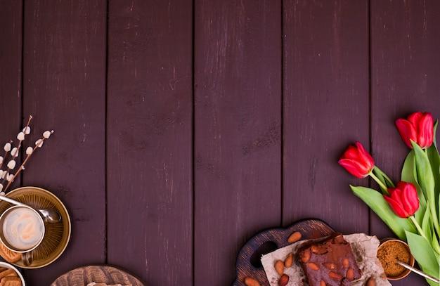 Expresso aromático fresco e brownie, sobre uma mesa de madeira. café da manhã de primavera, flores, tulipas, bolos e café. vista do topo. espaço livre para texto
