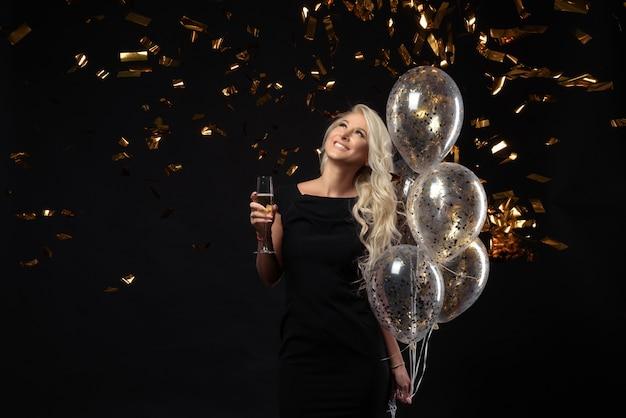 Expressões brilhantes de emoções felizes de uma incrível menina loira comemorando a festa. vestidos pretos luxuosos, sorrindo, uma taça de champanhe, enfeites dourados, balões, cabelos longos e cacheados