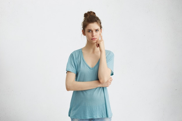 Expressões e emoções do rosto humano. mulher jovem pensativa em roupas casuais com o dedo na cabeça