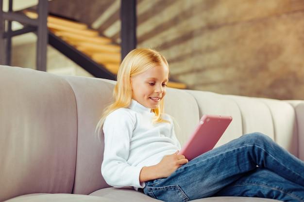Expressões faciais. criança em idade pré-escolar alegre sentada no sofá enquanto joga um jogo online