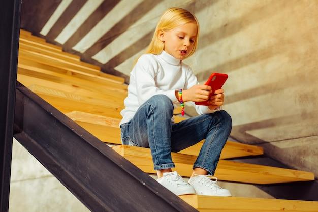 Expressões faciais. criança loira satisfeita baixando a cabeça enquanto olha para a tela de seu gadget