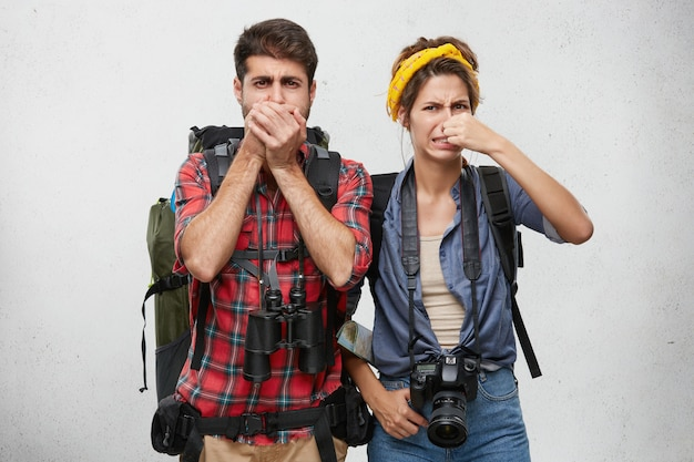Expressões faciais humanas, emoções e sentimentos. turismo e viagens. casal jovem ativo em roupas de turista, carregando mochilas, binóculos e câmera fotográfica beliscando o nariz por causa do fedor enojado
