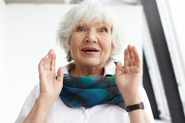 Expressões faciais humanas, emoções, sentimentos e reações. foto de uma elegante senhora caucasiana de meia-idade em roupas elegantes, com um olhar surpreso e espantado, recebendo notícias inesperadas