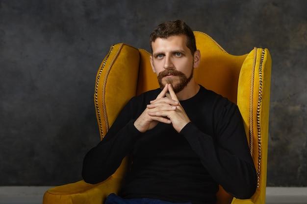 Expressões faciais humanas, sentimentos e linguagem corporal. jovem empresário barbudo na moda tocando o queixo, olhando pensativo enquanto pensa no plano de negócios e nas ideias na poltrona