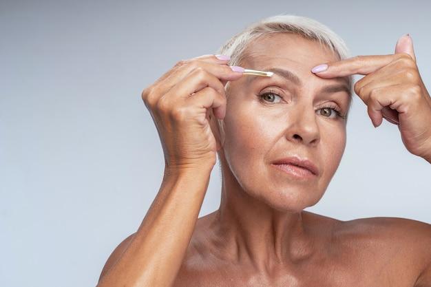 Expressões faciais. mulher séria usando uma pinça enquanto corrige as sobrancelhas