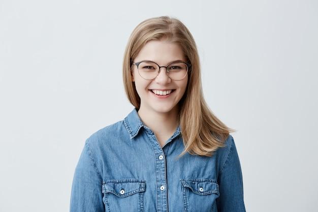 Expressões faciais positivas e emoções. aluna caucasiano atraente com cabelos lisos loiros em óculos elegantes, olhando e sorrindo amplamente durante uma boa conversa com alguém