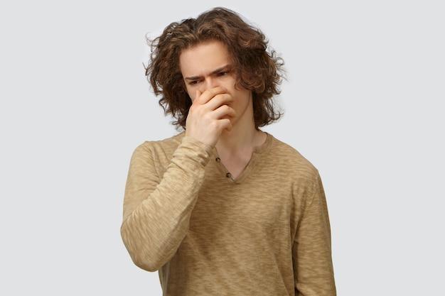 Expressões, sentimentos e reações humanas negativas. foto de um cara na moda com cabelo ondulado que vai vomitar, cobrindo a boca com a mão para suprimir o vômito por causa do cheiro nojento ou comida estragada